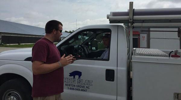 Wesley with Hog Slat service tech Dewayne Dunn