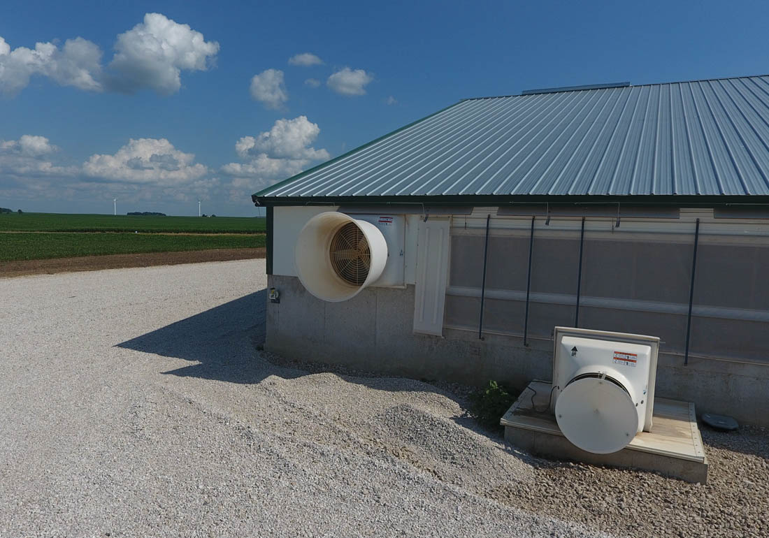 "36"" GrowerSELECT AirStorm fiberglass fan mounted to the sidewall of the barn and 24"" GrowerSELECT AirStorm fiberglass fan for deep pit ventilation with wind deflector."