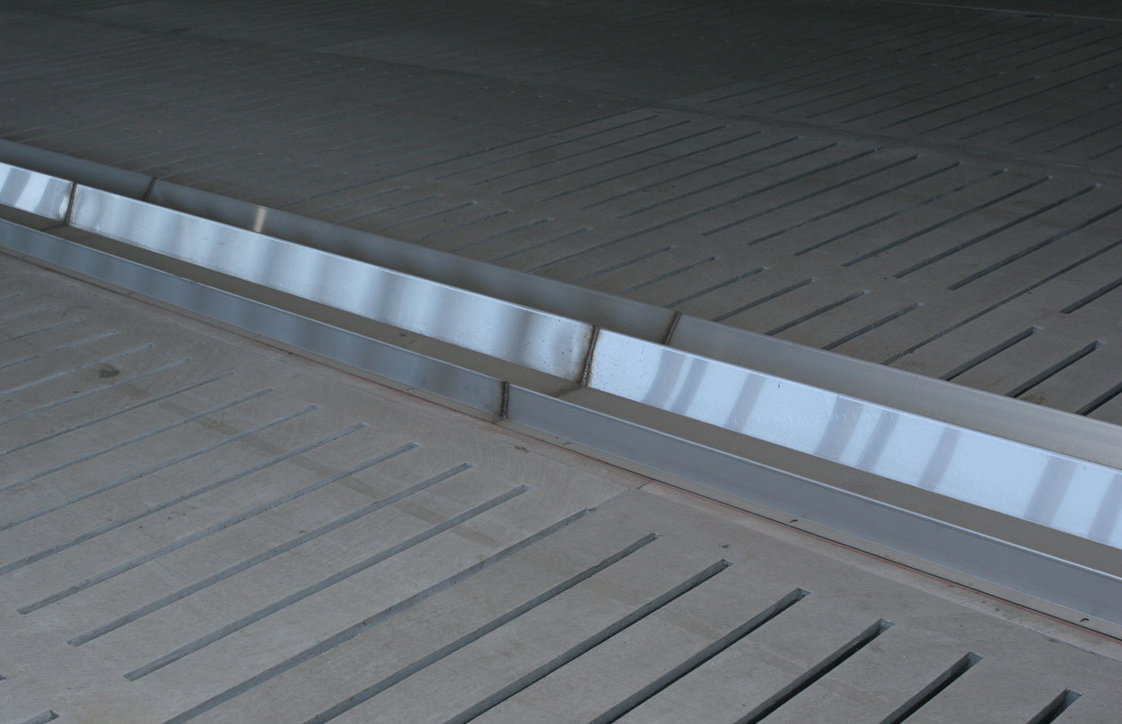 Stainless steel sow feeding trough can be installed with stanchion layouts to create feeding space on total slat barns and/or protect concrete surfaces from the damaging effects of feed and water over time. (Shown: Double-sided stainless steel sow feeding trough in a total slat floor barn.